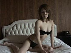 Eye catching Asian seductress lies on the bed wearing bikini