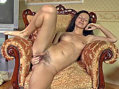 Dark-haired babe fingering her hairy muff on a chair